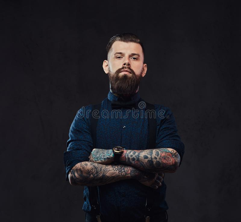 Portrait of a handsome old-fashioned hipster in a blue shirt and suspenders, standing with crossed arms in a studio. royalty free stock photography