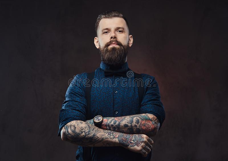 Portrait of a handsome old-fashioned hipster in a blue shirt and suspenders, standing with crossed arms in a studio. stock photos