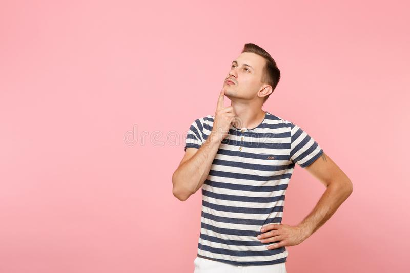 Portrait of handsome pensive young man in striped t-shirt thinking, put hand on chin face copy space isolated on royalty free stock photography