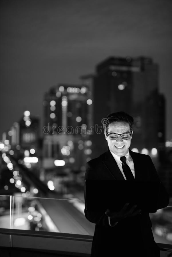 Handsome Persian businessman against view of the city at night stock photography