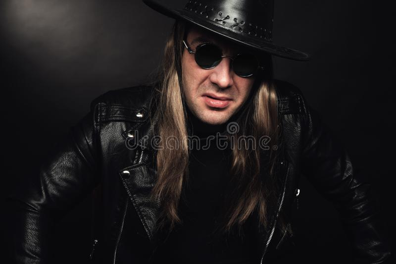 Portrait of handsome rocker in black leather jacket and sunglasses stock photos