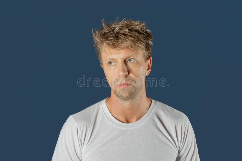 Portrait of handsome sad thoughtful man isolated over blue background royalty free stock image