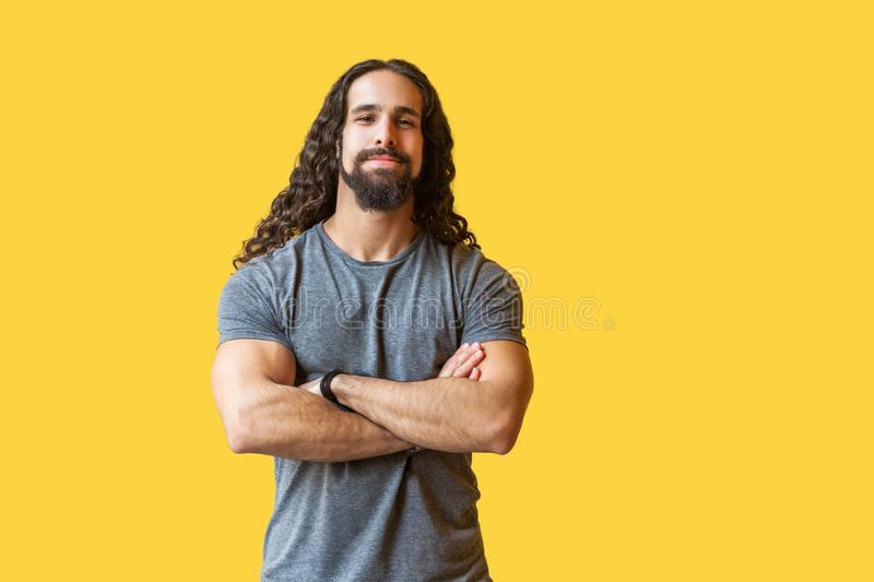 Portrait of handsome satisfied bearded young man with long curly hair in grey tshirt standing with crossed arms and looking at royalty free stock images