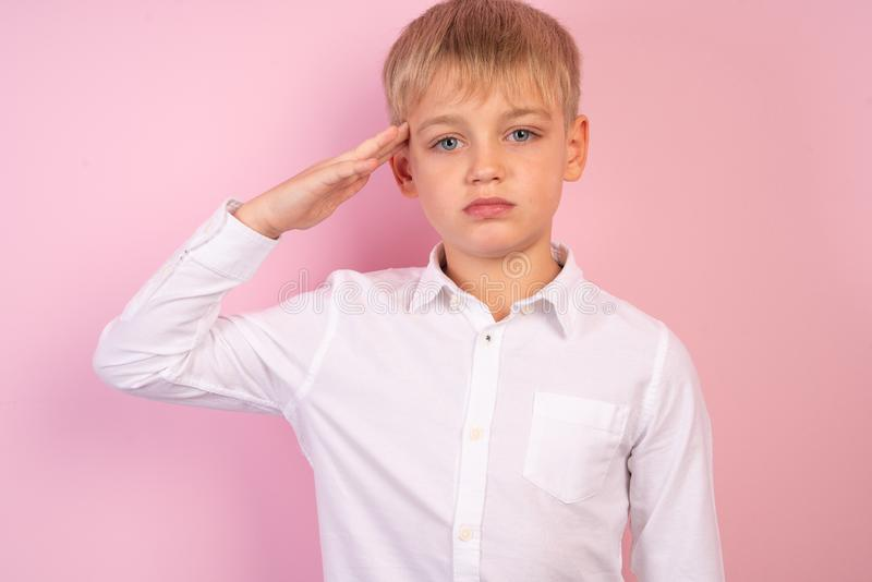 Portrait of handsome schoolboy. Young white haired guy with facial hair in white casual shirt saluting with hand at forehead stock image