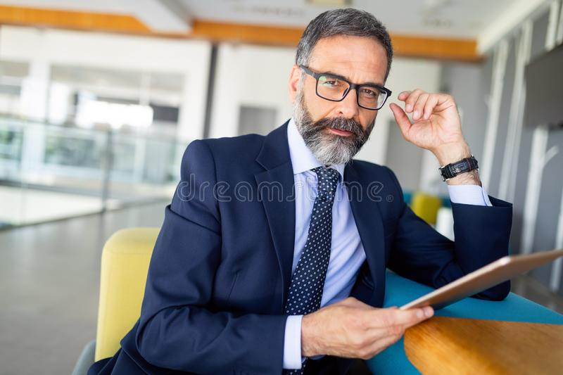 Portrait of handsome senior businessman with digital tablet in the modren office royalty free stock photography