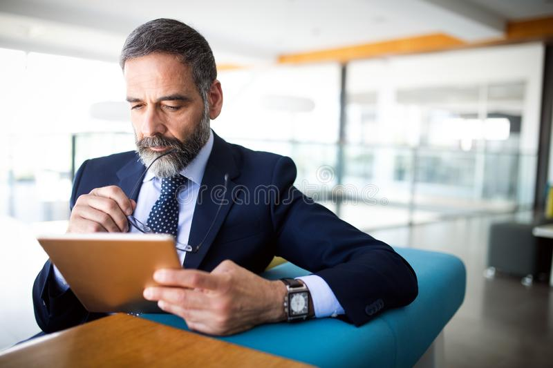 Portrait of handsome senior businessman with digital tablet in the modren office royalty free stock image