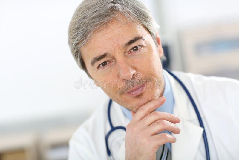 Portrait of handsome senior doctor stock image