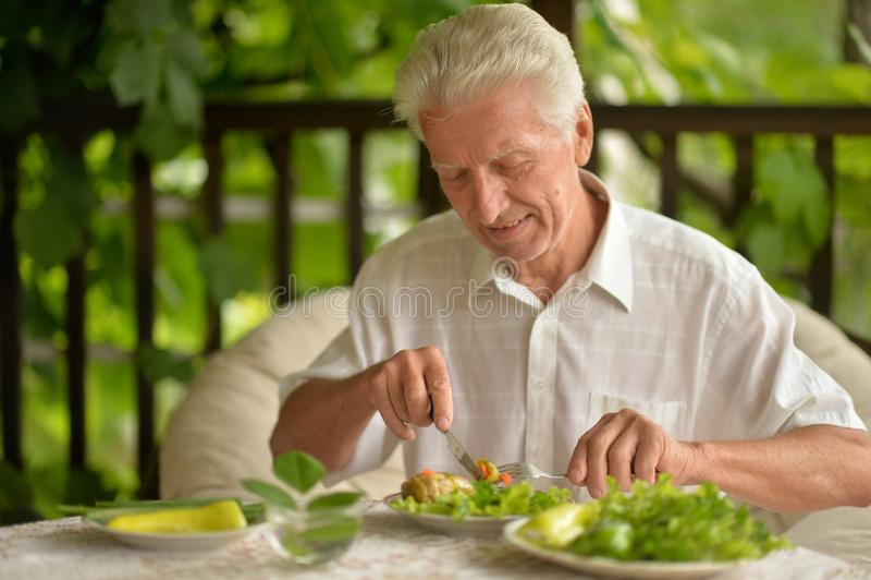 Portrait of handsome senior man eating stock photos