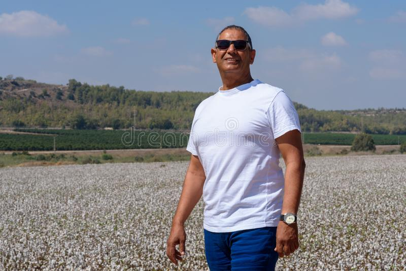 Portrait Of Handsome Senior Man In Outdoors. Sporty athletic elderly man on background of sky and cotton field. royalty free stock photography