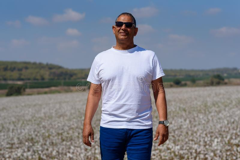 Portrait Of Handsome Senior Man In Outdoors. Sporty athletic elderly man on background of sky and cotton field. stock images