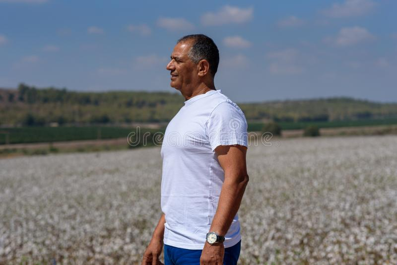 Portrait Of Handsome Senior Man In Outdoors. Sporty athletic elderly man on background of sky and cotton field. stock photo