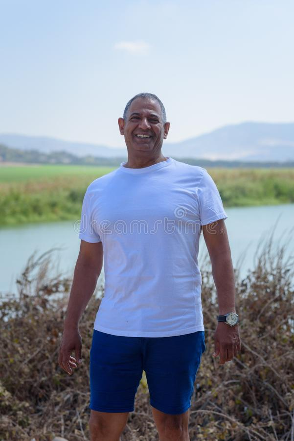 Portrait Of Handsome Senior Man Outdoors. Sporty athletic elderly man on background of sky and lake. royalty free stock image