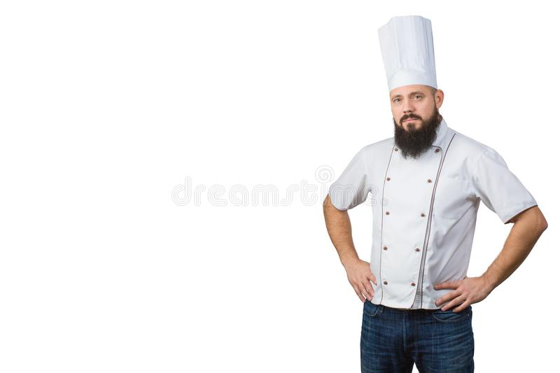 Portrait of handsome bearded male chef in uniform hands on waist isolated on white background, copy space on side. royalty free stock photography