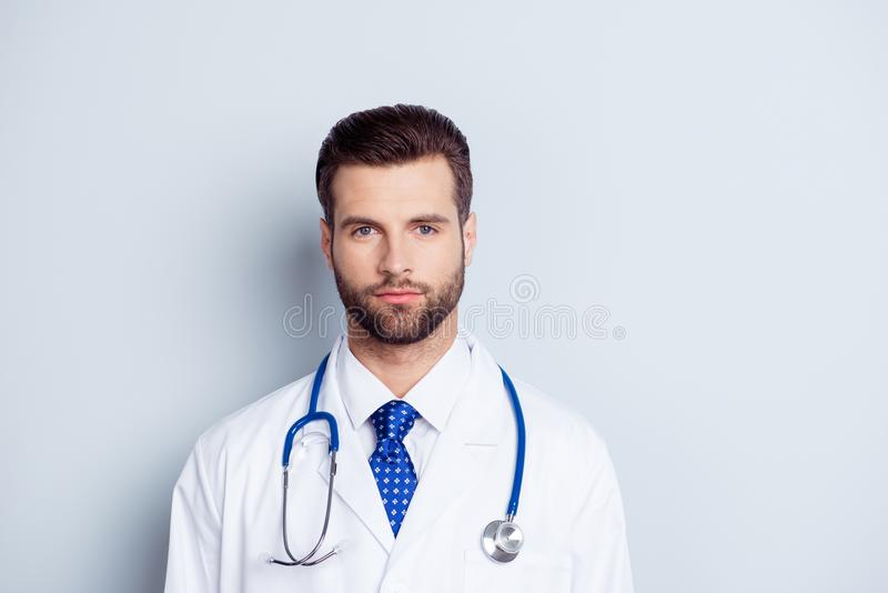 Portrait of handsome serious doctor in white coat and stethoscope on neck isolated on grey background royalty free stock photos