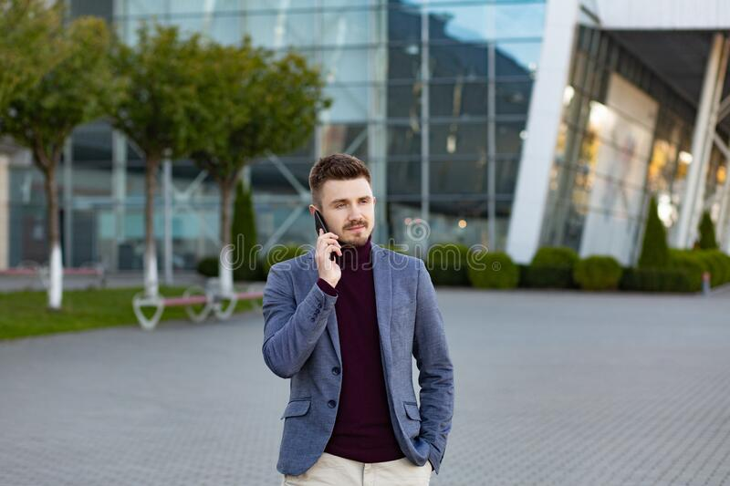 Portrait of handsome serious man in casual wear holding smartphone. Successful manager makes a call. Young businessman. Talking on the phone, standing on city stock photos
