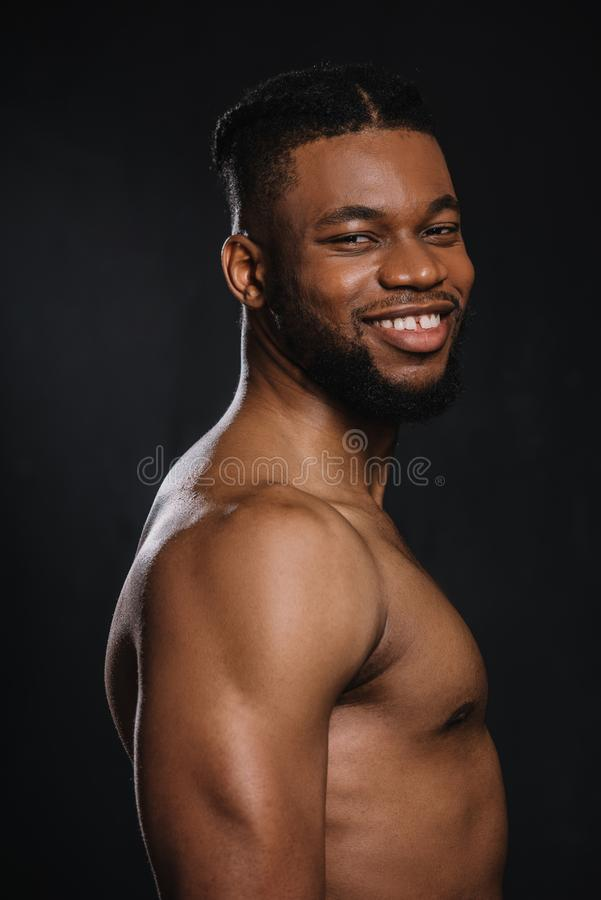 portrait of handsome shirtless young muscular african american man smiling at camera stock photo