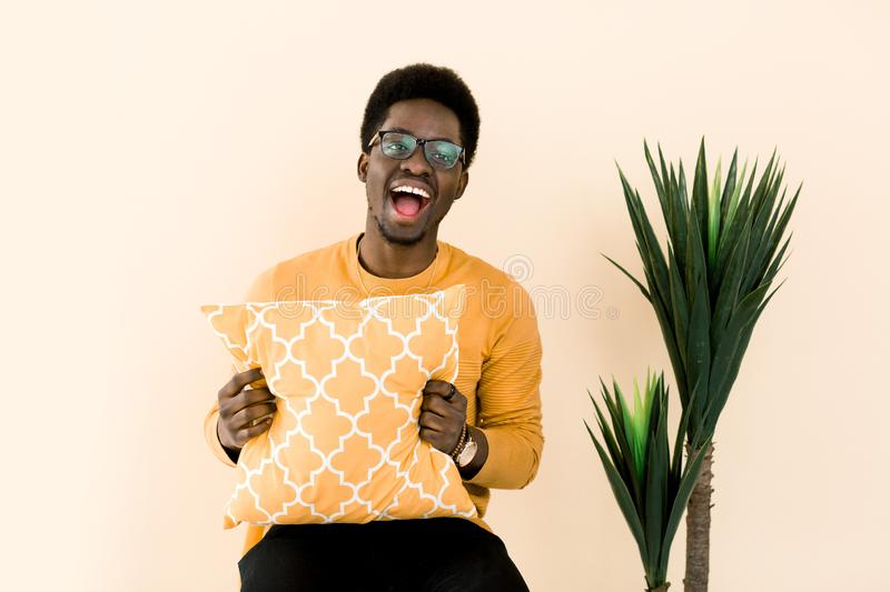 Portrait of handsome shocked african american man laughing with surprised and happy face. African guy in yellow sweater stock images