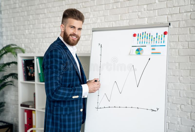 Portrait of handsome smart speaker expressing his ideas about new business project and pointing on graphs stock photo