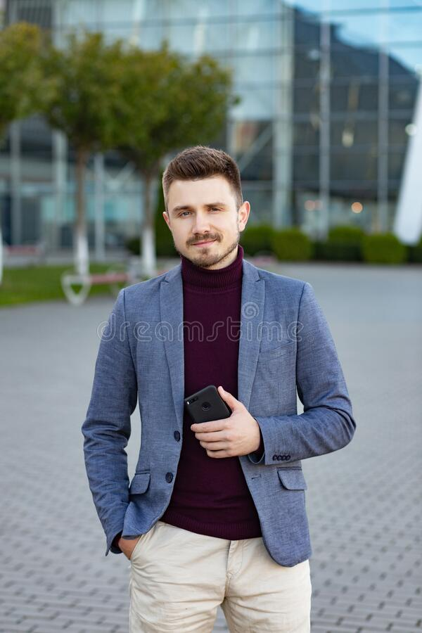 Portrait of handsome smiling man in casual wear holding smartphone. Young businessman analyzes the results of important. Phone conversation. Young man standing royalty free stock photos