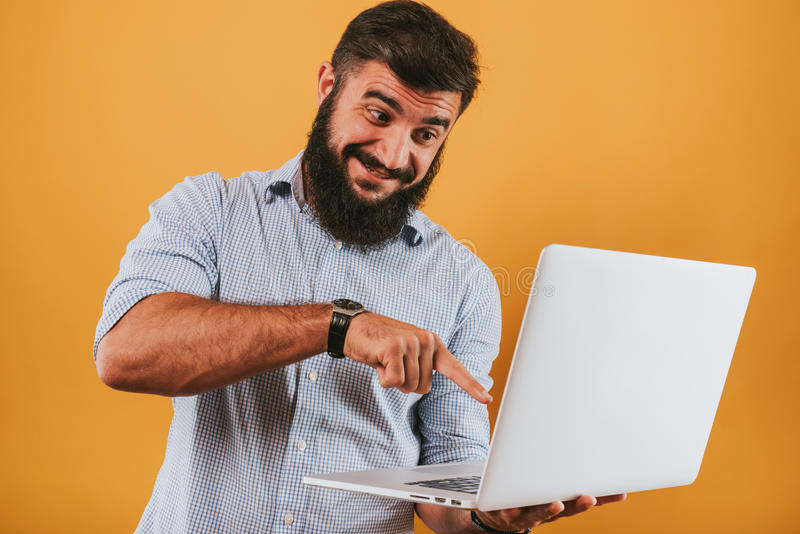 Portrait of handsome smiling man isolated on yellow studio background posing to the camera and making funny faces got an idea stock photography