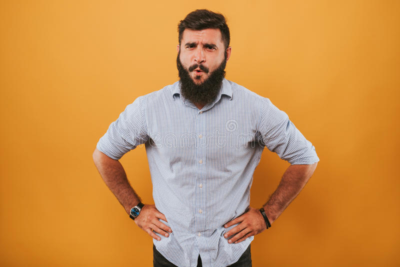 Portrait of handsome smiling man isolated on yellow studio background posing to the camera and making funny faces got an idea royalty free stock photos