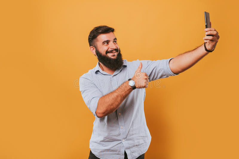 Portrait of handsome smiling man isolated on yellow studio background posing to the camera and making funny faces got an idea stock photos
