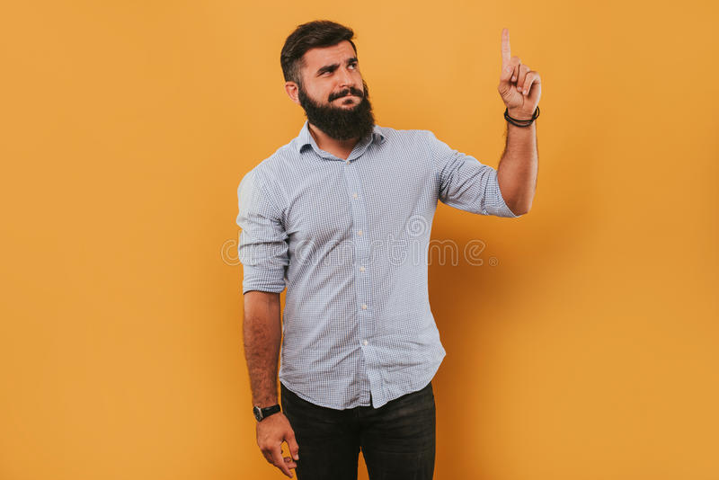 Portrait of handsome smiling man isolated on yellow studio background posing to the camera and making funny faces got an idea stock image