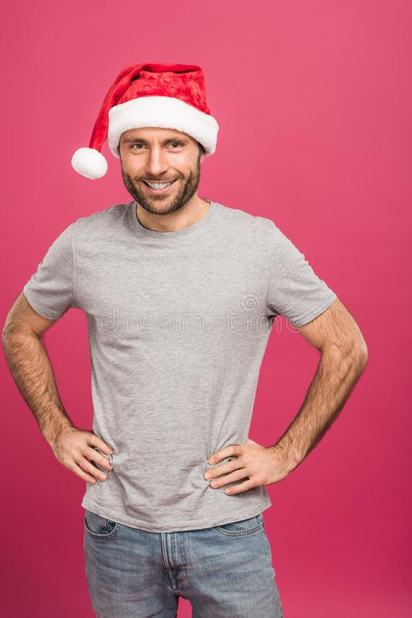 portrait of handsome smiling man in santa hat at christmastime, isolated stock photography