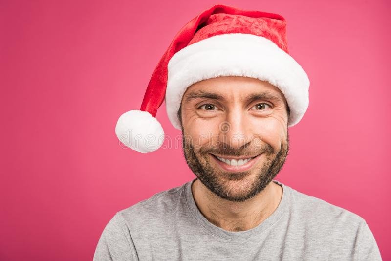 portrait of handsome smiling man in santa hat, isolated stock image