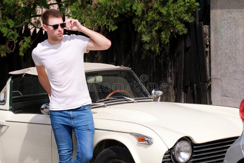 Portrait of a handsome smiling man with sunglasses, male model posing in urban city street next his car. royalty free stock image