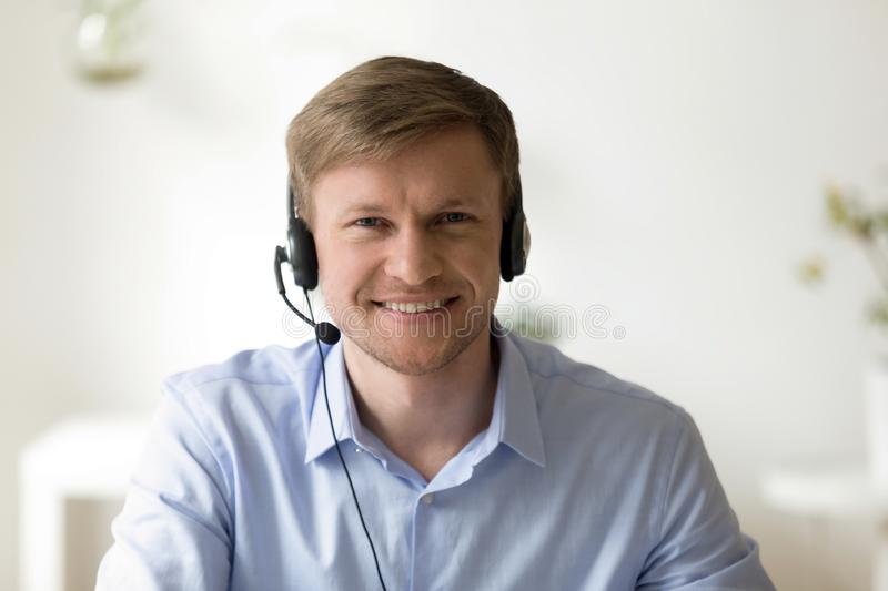 Portrait of handsome smiling man working in headphones at office royalty free stock photography