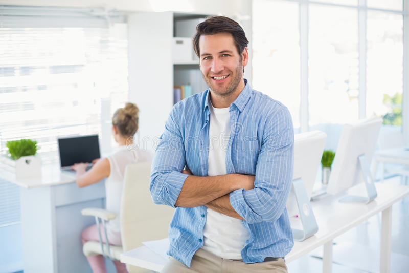 Portrait of handsome smiling photo editor with arms crossed. In office stock image