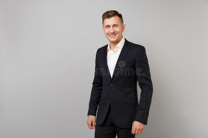 Portrait of handsome smiling young business man in classic black suit, white shirt standing isolated on grey wall stock images