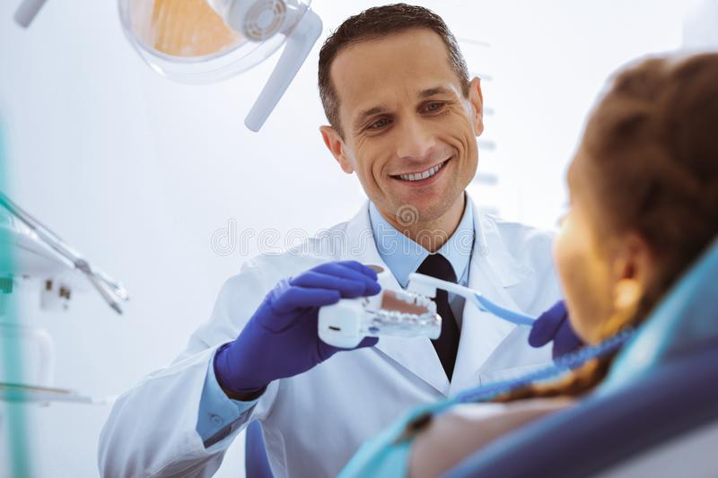Portrait of handsome stomatologist that cleaning teeth. Correct movements. Cheerful medical worker keeping smile on face while speaking with his patient royalty free stock photography