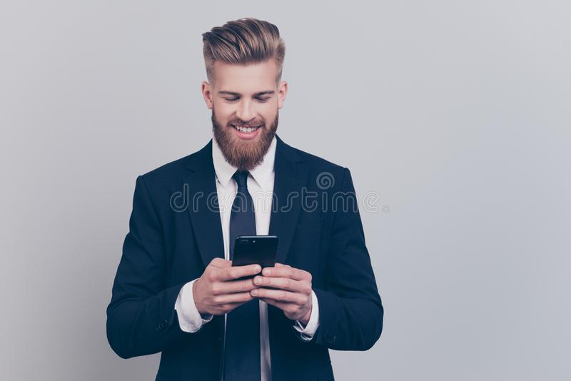Portrait of handsome with stylish hairdo cheerful funny excited. Financier using smartphone playing online games receiving getting writing sms updating his royalty free stock images