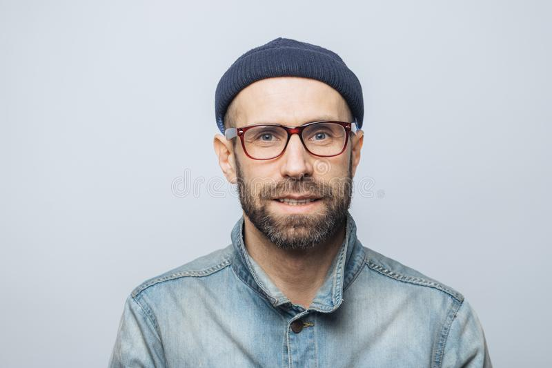 Portrait of handsome stylish male journalist wears eyewear, fashionable hat and denim jacket, poses against white studio backgroun royalty free stock photos