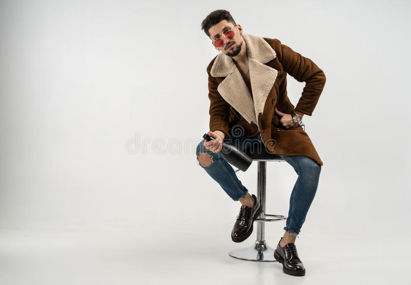 Portrait of handsome stylish model male in coat and sunglasses stock photo