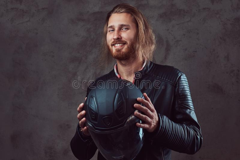 Portrait of a handsome stylish redhead biker in a black leather jacket, holds motorcycle helmet, posing in a studio. stock photos