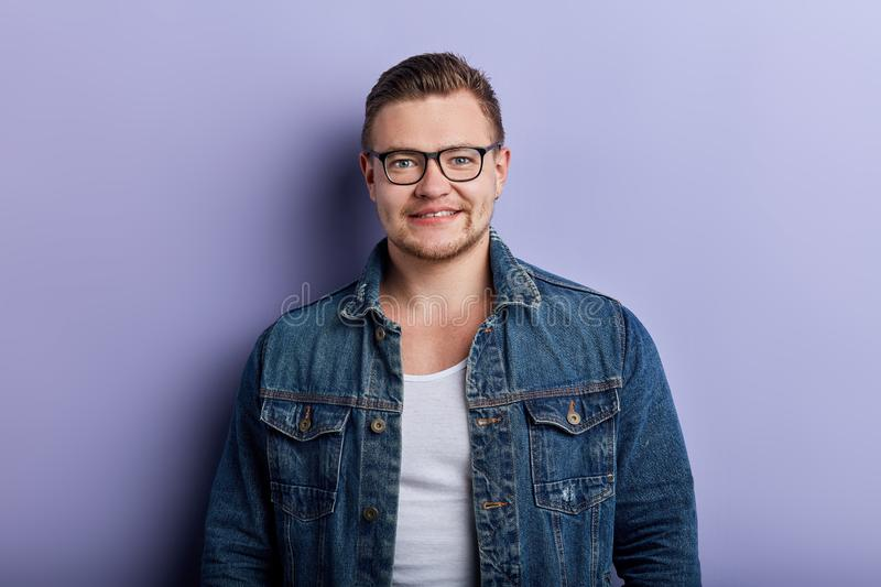 Portrait of handsome stylish young man in glasses posing to the camera stock photography