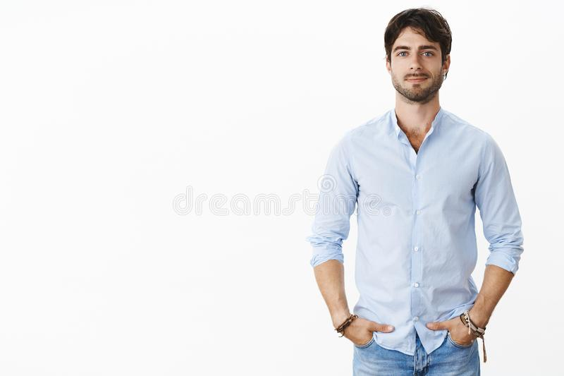 Portrait of handsome successful male entrepreneur in stylish shirt smiling self-assured standing in confident pose with royalty free stock images