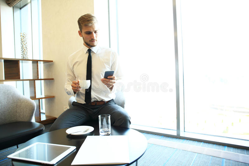 Portrait of handsome successful man drink coffee sitting in coffee shop, business man having breakfast at hotel lobby. Portrait of handsome successful man drink royalty free stock image