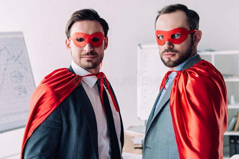 portrait of handsome super businessmen in masks and capes royalty free stock photos