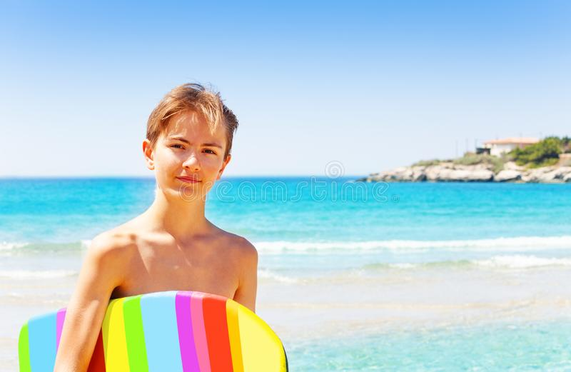 Handsome teenage boy with swim board on the beach stock images