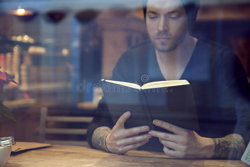 Portrait of handsome white hipster man read a book in cafe near window stock image