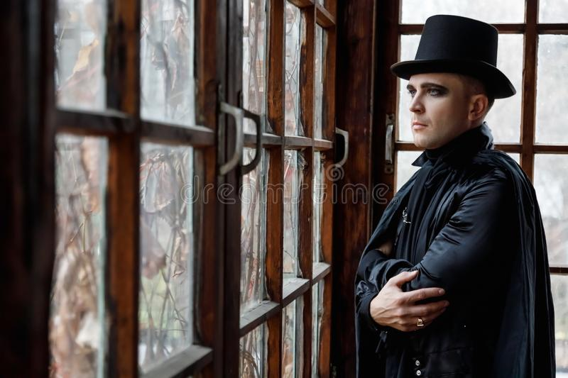 Portrait of a handsome young adult man in old fashioned vampire style clothes stock photos
