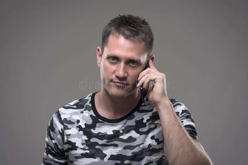 Portrait of handsome young adult man talking on the mobile phone and smiling looking at camera stock image