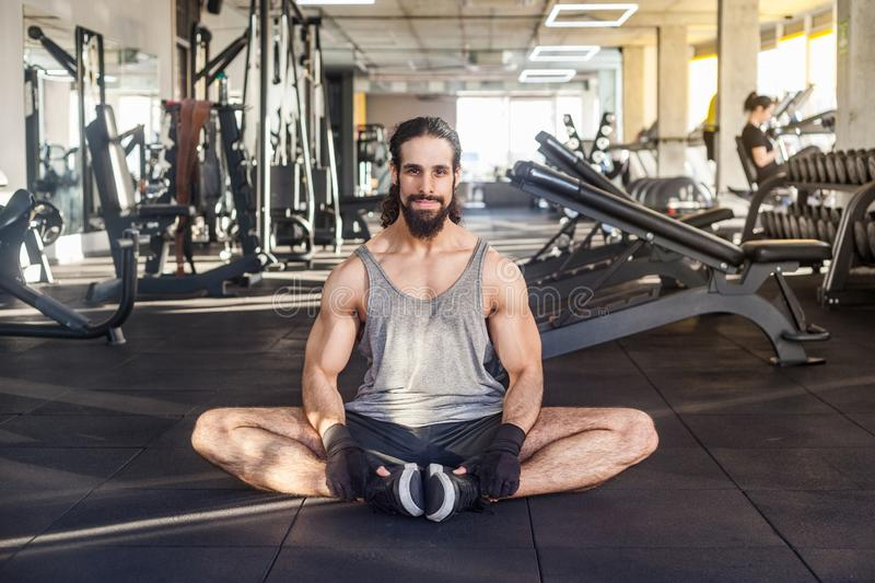 Portrait of handsome young adult muscular body man with long curly hair working out in gym, sitting on floor in pose butterfly,. Relaxation after training royalty free stock image