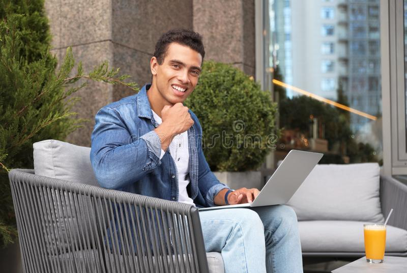 Portrait of handsome young -American man with laptop in outdoor cafe stock image
