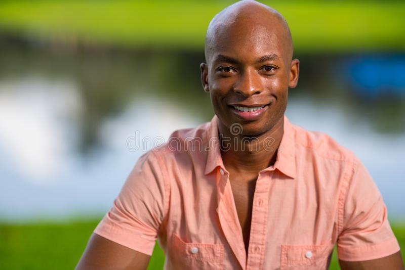 Portrait handsome young African American man smiling at camera. Man wearing a pink button shirt unbuttoned half way stock photo