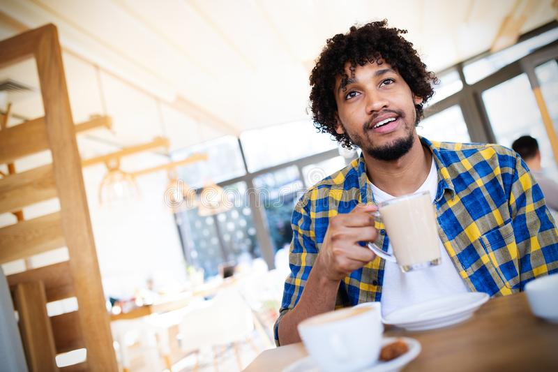 Portrait of handsome young african man relaxing with a cup of coffee in cafe royalty free stock image
